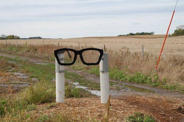 Monumento com óculos de Buddy Holly próximo ao lugar do acidente aéreo que o matou