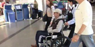 Eric Clapton em cadeira de rodas no aeroporto