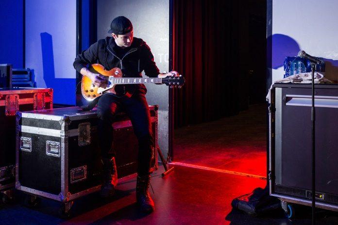 Roadie afina guitarra no backstage