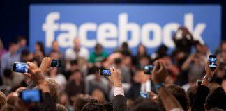Pessoas fotografando o logo do Facebook